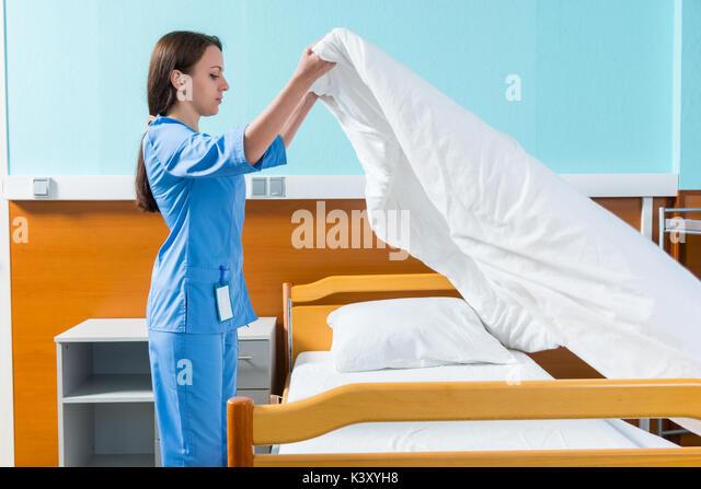 Junge Krankenschwester in Blau unifrom Ändern Bettwäsche von Krankenhausbett in die Krankenstation. Healthcare Stockbild