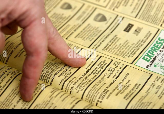 Finger wandern durch kleine Single Entry Business Listings in Gelbe Seiten, Telefonbuch Papier Ausgabe Großbritannien Stockbild