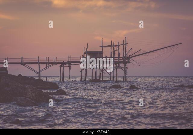 Nostalgischer Abend an der Adria. Lonely womant steht an trabocchi Pier Stockbild