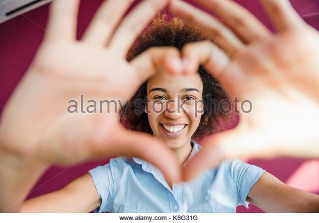 Porträt der jungen Frau, die Herzform mit Händen und Fingern. Stockbild