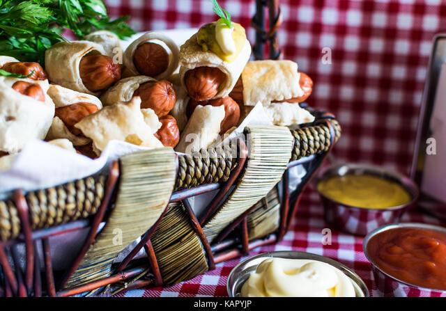 Weidenkorb mit Artisan mini Hot Dogs (Würstchen im Teig) mit Senf, Mayonnaise auf einem karierten Hintergrund Stockbild