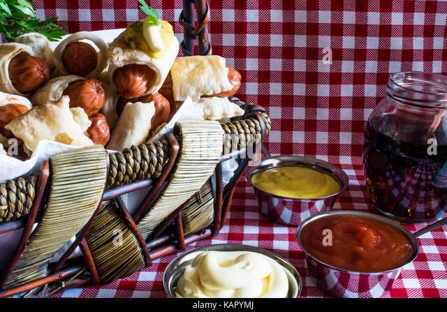 Weidenkorb mit Mini artisan Hot Dogs (Würstchen im Teig) mit Senf, Mayonnaise und Cola auf eine karierte Hintergrund Stockbild