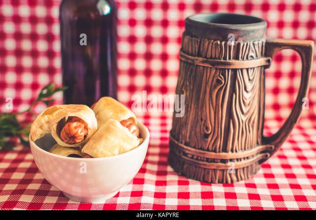 Platte Mini hot dogs Hausgemachte (Würstchen in Blätterteig) auf Serviette mit einer Flasche dunkles Bier Stockbild