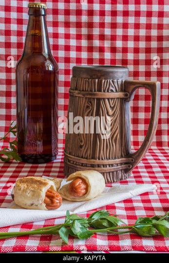 Hausgemachte Mini Hot Dogs (Würstchen in Blätterteig) auf Serviette mit einer Flasche dunkles Bier und Stockbild