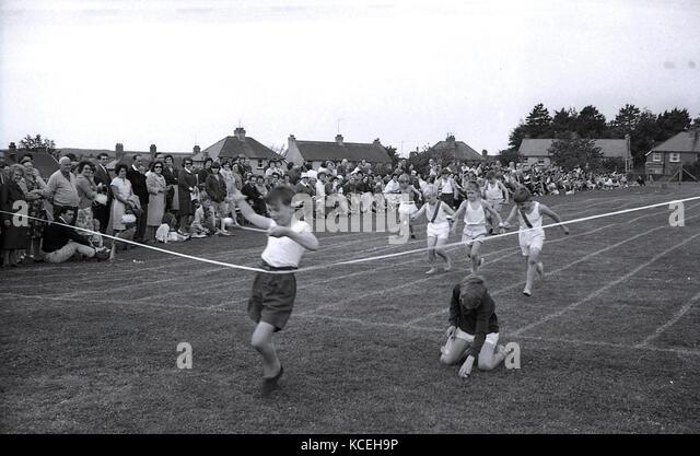1960, historische Bild von kleinen Jungen, die sich in einem Ei-und-löffel Rennen an eine Grundschule Sport Stockbild