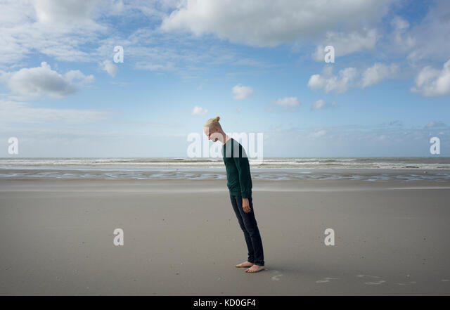 Junge am Strand, nach vorne in den stürmischen Wind, Gravelines, nord-Pas-de-Calais, Frankreich Stockbild