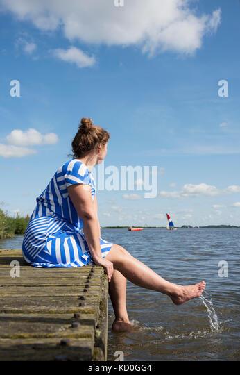 Frau sitzt auf der Jetty in der friesischen Seenplatte in vintage Kleid, sneek, friesland, Niederlande Stockbild