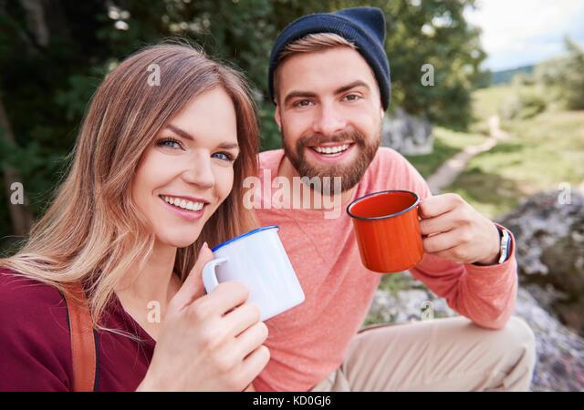 Portrait von Paar hält Emaille Becher in die Kamera lächeln, Krakow, Malopolskie, Polen suchen, Europa Stockbild