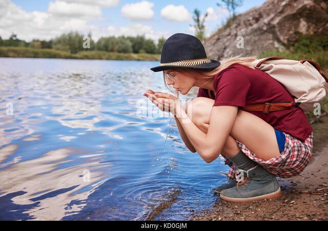 Frau Hockend von Waters Edge Schaufeln das Wasser in die Hände, Krakow, Malopolskie, Polen, Europa Stockbild