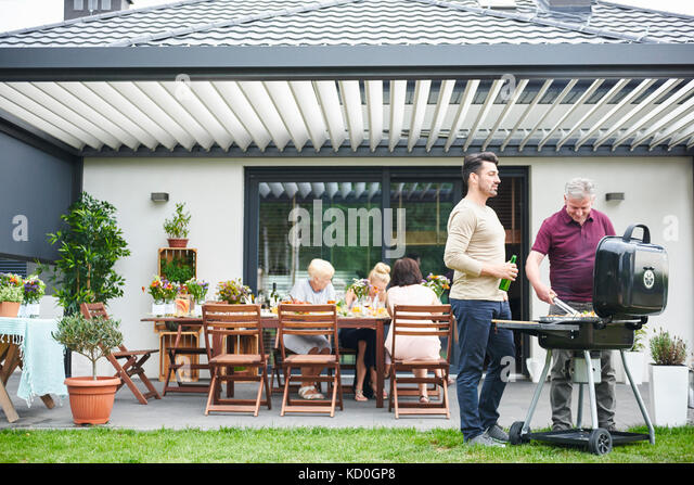 Zwei Männer auf der Terrasse grillen bei Familie Mittagessen Stockbild