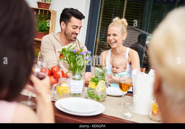 Paar mit Baby Tochter an Familie Mittagessen auf der Terrasse Tisch Stockbild