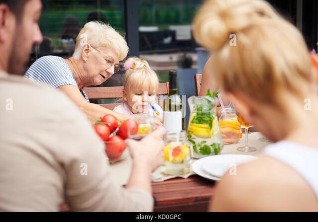 Ältere Frau mit Kleinkind Enkelin bei Familie Mittagessen auf der Terrasse Tisch Stockbild