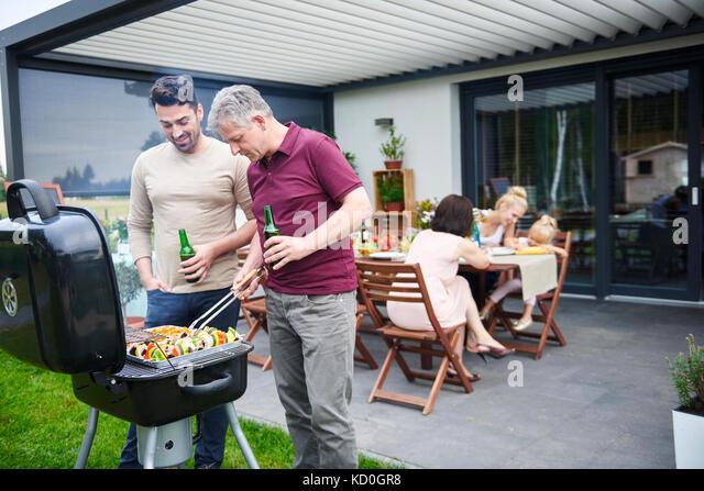 Reifen und Mitte der erwachsene Mann Grillen bei Familie Mittagessen auf der Terrasse Stockbild