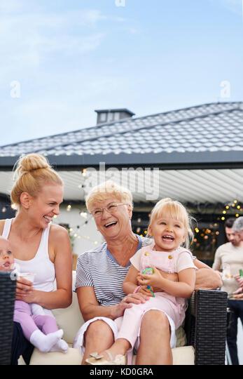 Drei generation Frauen mit Kindern in den Runden bei Familie Mittagessen auf der Terrasse Stockbild
