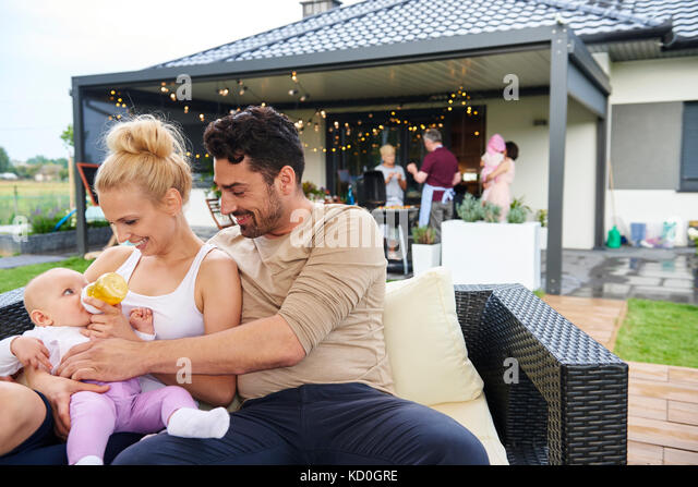 Paar feeding baby Tochter an Familie Mittagessen auf der Terrasse Stockbild
