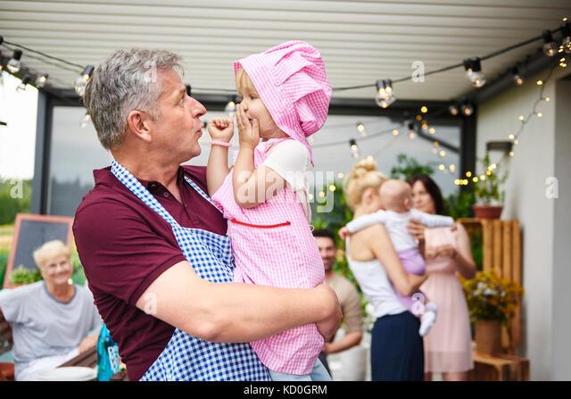 Reifer mann Gesichter bei kleinkind Enkelin bei Familie Mittagessen auf der Terrasse Stockbild