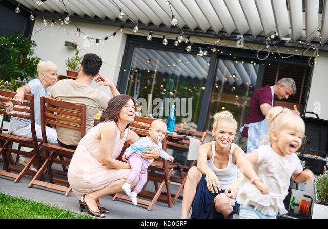 Weibliche Kleinkind spielen an drei Generation Familie Mittagessen auf der Terrasse Stockbild