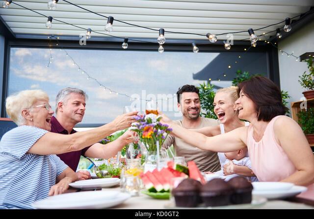 Drei Generationen der Familie einen Wein Toast beim Mittagessen auf der Terrasse Stockbild