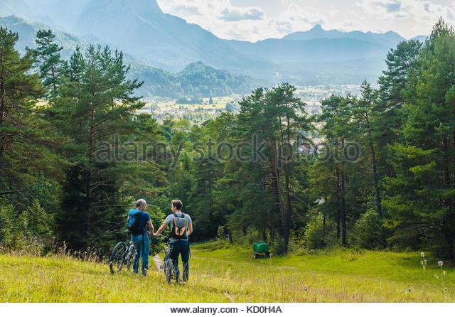 Vater und Sohn, in ländlicher Umgebung, Wandern mit Fahrrädern, Rückansicht, elbsee, Bayern, Deutschland Stockbild