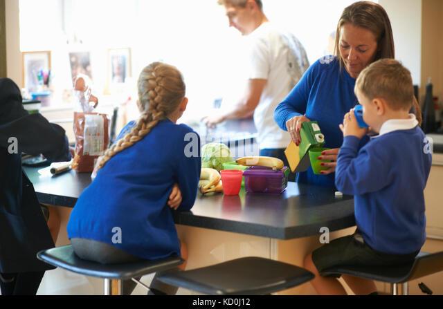 Mutter gießen Saft für Ihre Schule die Kinder in der Küche Stockbild