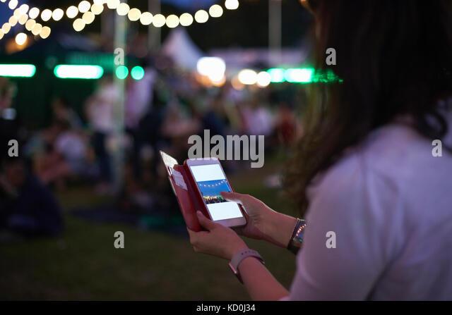 Reife Frau Überprüfung smartphone Fotos bei Nacht Markt Festival in Park, London, UK Stockbild