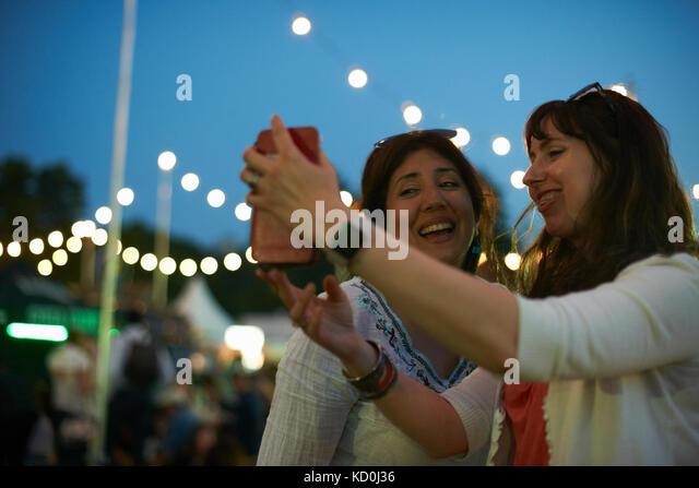 Zwei reife weibliche Freunde, Smartphone selfie bei Nacht Markt Festival in Park, London, UK Stockbild