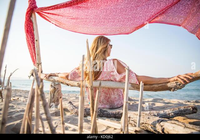 Ansicht der Rückseite Frau sitzt am Strand entspannen, Palma de Mallorca, Balearen, Spanien, Europa Stockbild