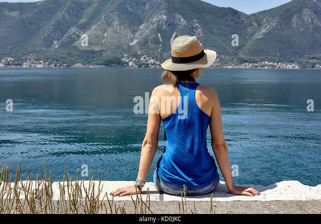 Ansicht der Rückseite Frau in Trilby sitzen auf Waterfront mit Blick auf die Bucht von Kotor, Montenegro Stockbild
