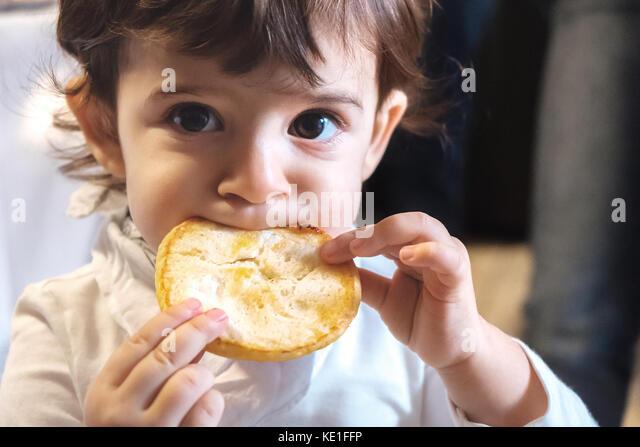 Baby Kind essen Kohlenhydrate - Neugeborene essen Gesicht Nahaufnahme Portrait - ungesunde Ernährung für Stockbild