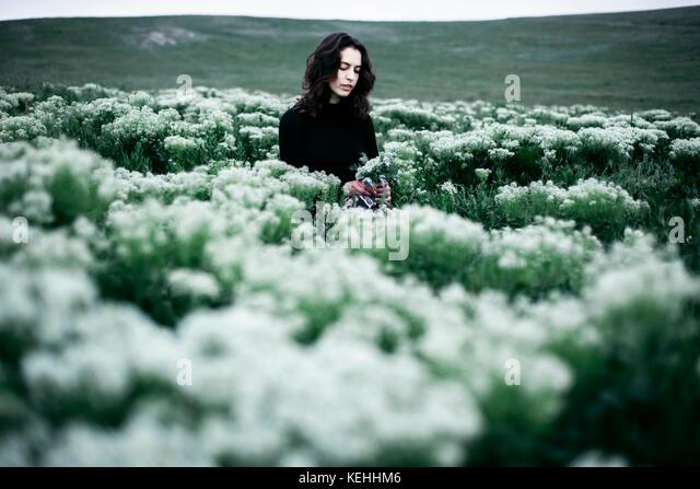 Kaukasische Frau, die auf dem Gebiet der Wildblumen Stockbild