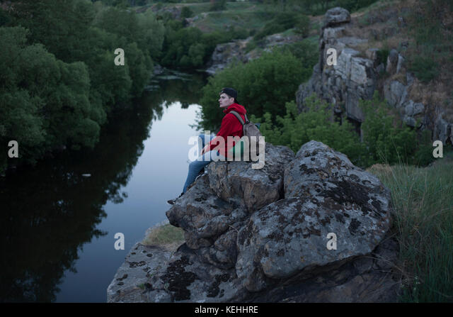Kaukasische Mann sitzt auf einem Felsen in der Nähe des Flusses Stockbild