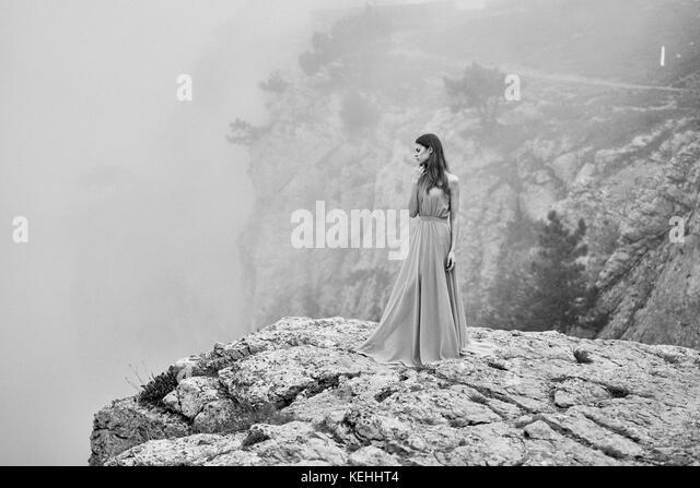 Frau in Kleid steht auf Rock im Nebel Stockbild