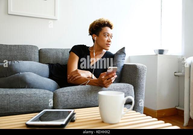 Gemischte Rasse Frau Festlegung auf dem Sofa hören Ohrhörer Stockbild