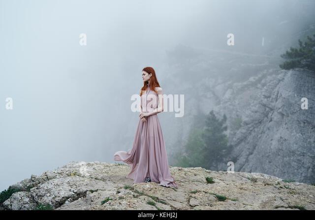 Kaukasische Frau in Kleid auf Rock im Nebel Stockbild