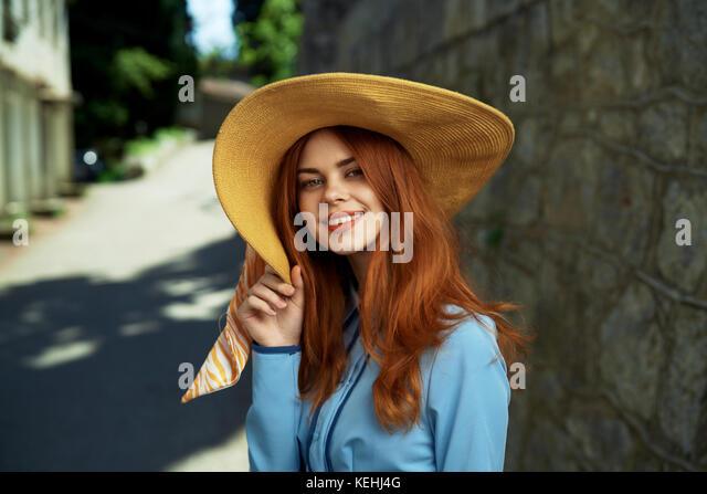 Lächelnd kaukasische Frau mit Hut in der Nähe von Stone Wall Stockbild
