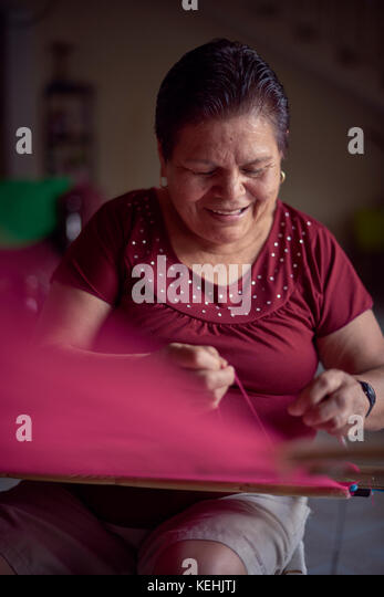 Hispanic Frau Weben am Webstuhl Gewebe Stockbild