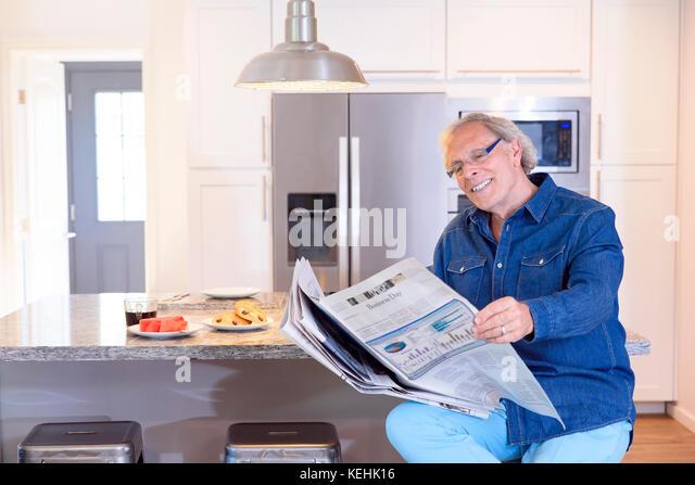 Kaukasische Mann liest Zeitung in der Küche Stockbild