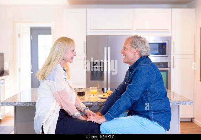 Kaukasische Paar hält Hände in der Küche Stockbild