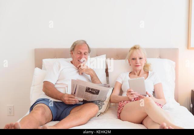 Kaukasische Paar lesen Zeitung und digitale Tablet im Bett Stockbild