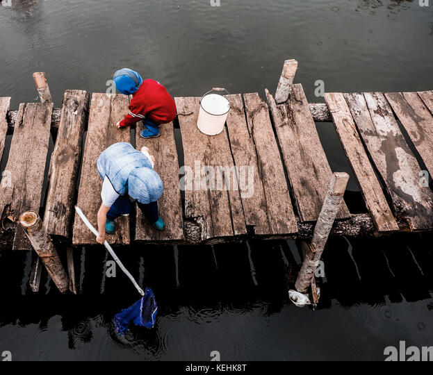 Jungen spielen auf Holz- Dock Stockbild