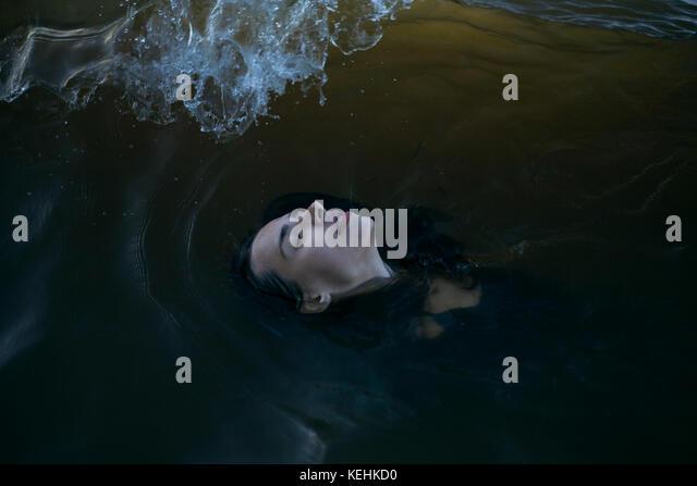 Kaukasische Frau floating im Ozean mit geschlossenen Augen Stockbild