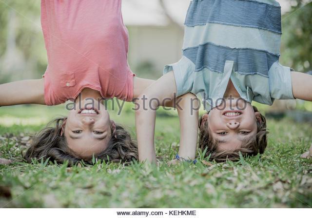 Hispanic Bruder und Schwester headstands im Gras Stockbild