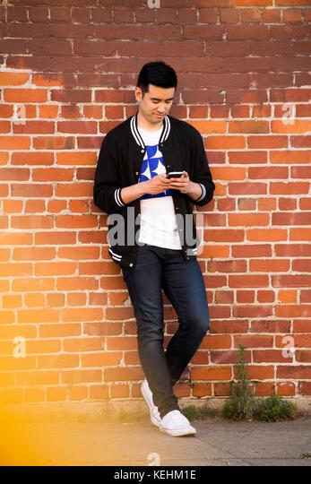 Chinesischer Mann lehnte sich auf Mauer SMS auf Handy Stockbild