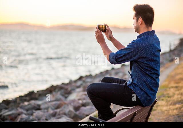 Chinesischer Mann sitzt auf der Bank fotografieren Ozean mit Handy Stockbild