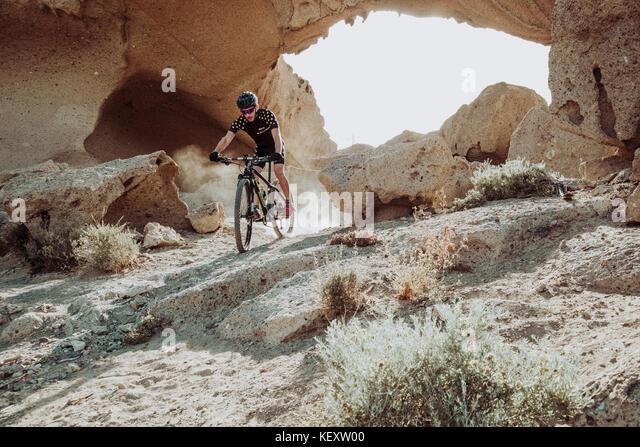 Mann, sein Mountainbike in der Wüste, Teneriffa, Kanarische Inseln, Spanien Stockbild