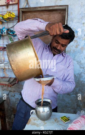 Chai wallah Chai aus Messing Pan, mit Zange, durch Sieb in Zinn Schiff, im Dorf Markt, diggi Diggi, Rajasthan, Indien, Stockbild