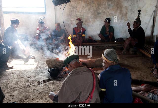 Naga Männer sitzen plaudernd Um die zentrale Feuer in ihrem Dorf murung (Rathaus), hongphui Dorf, Nagaland, Stockbild