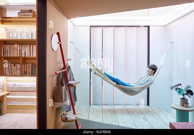 Zimmer Ansicht mit Bücherregal und Hängematte. Der Stack - mini Living urban Kabine, London, Großbritannien Stockbild