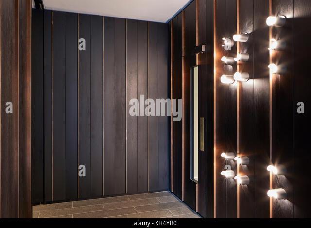 Holztäfelung und Beleuchtungskörper in Gebäude Flur. 55 Victoria Street, London, Großbritannien Stockbild