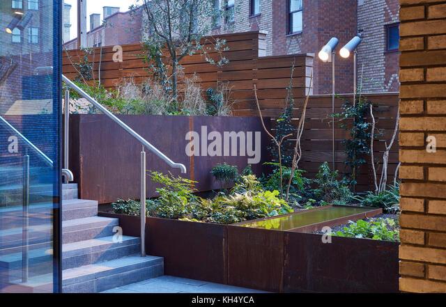 Angelegter Garten mit Außenbeleuchtung und Metall Garten Betten. 55 Victoria Street, London, Großbritannien Stockbild